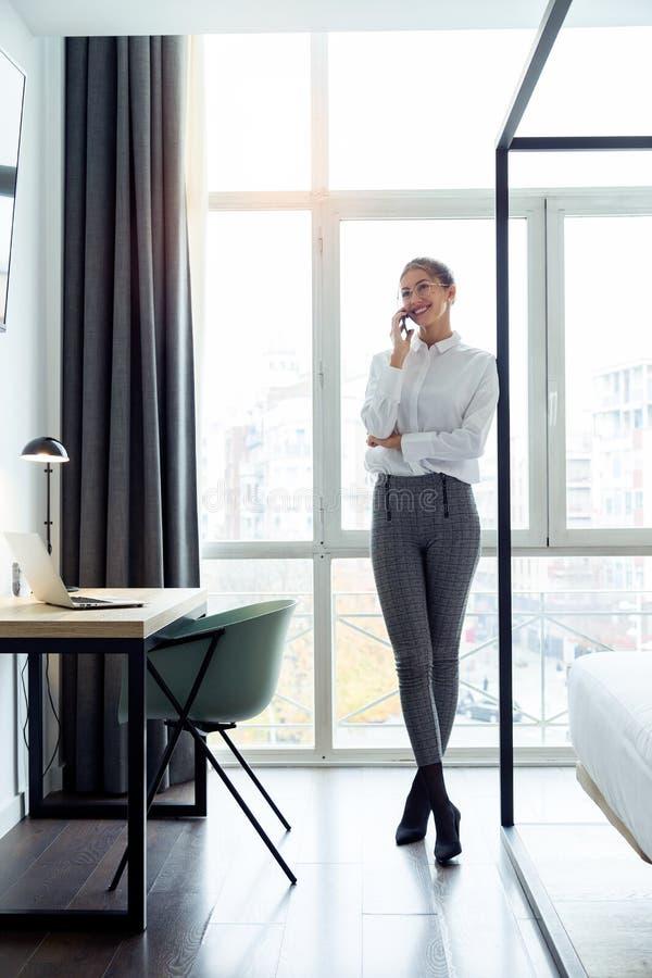 Empresaria joven elegante que habla con su situación del smartphone cerca de la ventana en la habitación fotografía de archivo libre de regalías