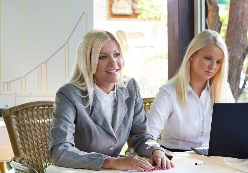 Empresaria joven en el café que habla mientras que el otro sigue el representante imágenes de archivo libres de regalías