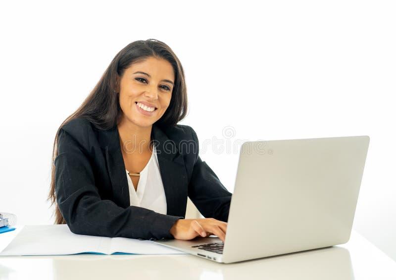 Empresaria joven feliz que trabaja en su ordenador en su escritorio en satisfecho en el trabajo y la mujer acertada aislados en b foto de archivo