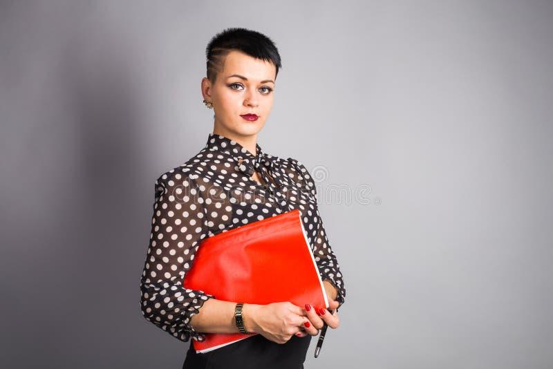 Empresaria joven hermosa con el caso del documento Fondo gris, con el espacio de la copia imagen de archivo