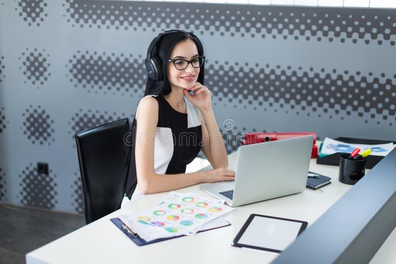 Empresaria joven hermosa en vestido, auriculares y gla negros imágenes de archivo libres de regalías