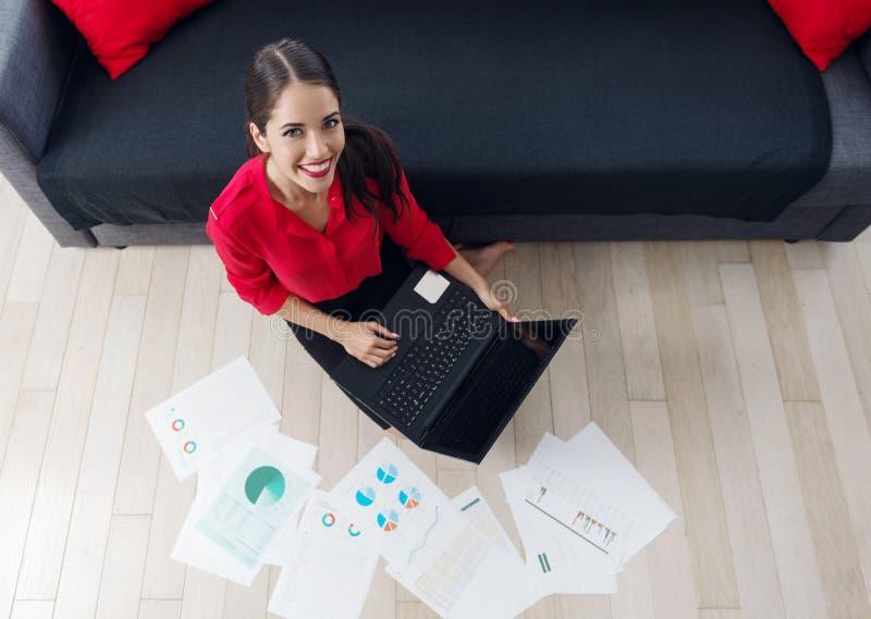 Empresaria joven hermosa que se sienta en el piso, usando un ordenador portátil fotografía de archivo