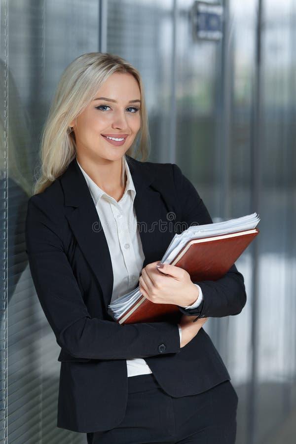 Empresaria joven hermosa que sonríe y que se coloca con la carpeta en la oficina mirada de la cámara fotografía de archivo libre de regalías
