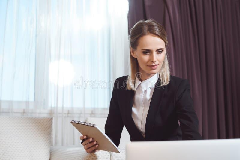 empresaria joven hermosa que sostiene el cuaderno y que usa el ordenador portátil fotos de archivo