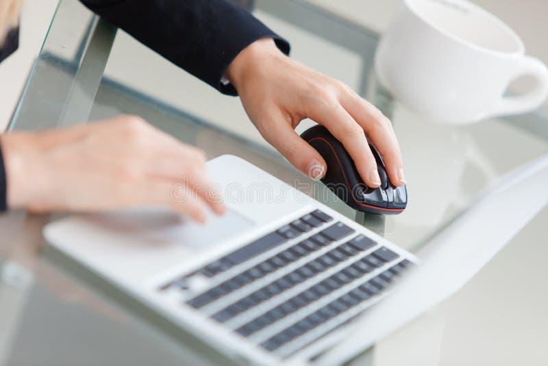 Empresaria joven hermosa que usa el ordenador portátil imagen de archivo libre de regalías
