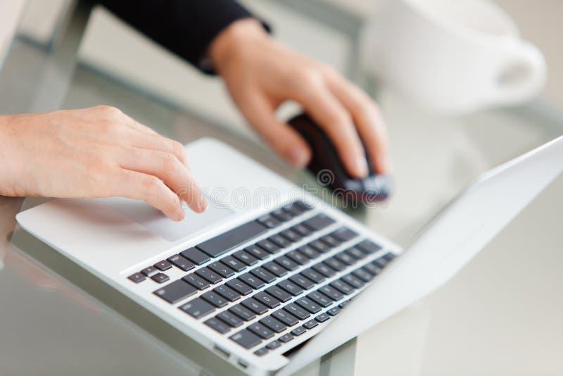Empresaria joven hermosa que usa el ordenador portátil fotografía de archivo libre de regalías