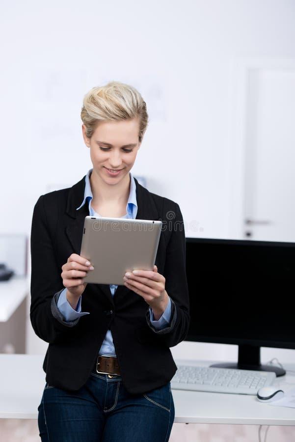 Empresaria joven Holding Digital Tablet en oficina fotografía de archivo libre de regalías