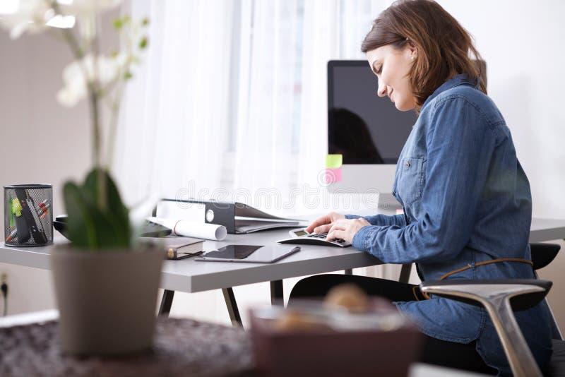 Empresaria joven ocupada Sitting en su mesa de trabajo fotografía de archivo libre de regalías