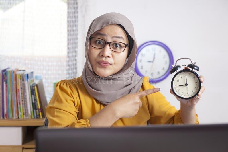 Empresaria joven Pointing en el reloj, expresi?n enojada imagen de archivo