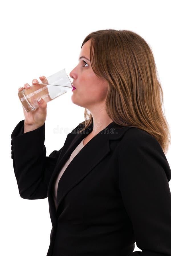 Empresaria joven que bebe un vidrio de agua imagenes de archivo