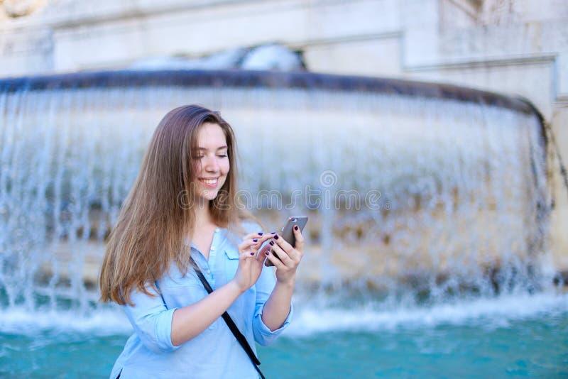 Empresaria joven que charla por smartphone en fondo de la fuente del Trevi imagen de archivo libre de regalías