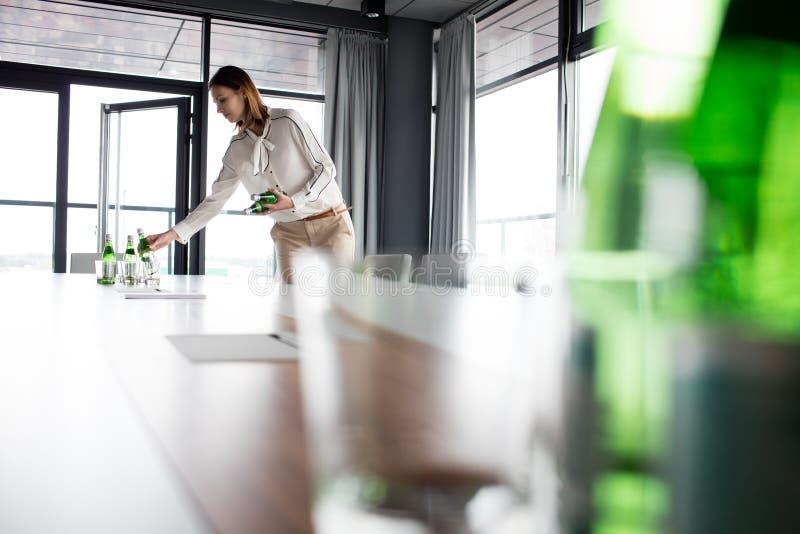 Empresaria joven que coloca las botellas de agua en la mesa de reuniones en oficina imagenes de archivo
