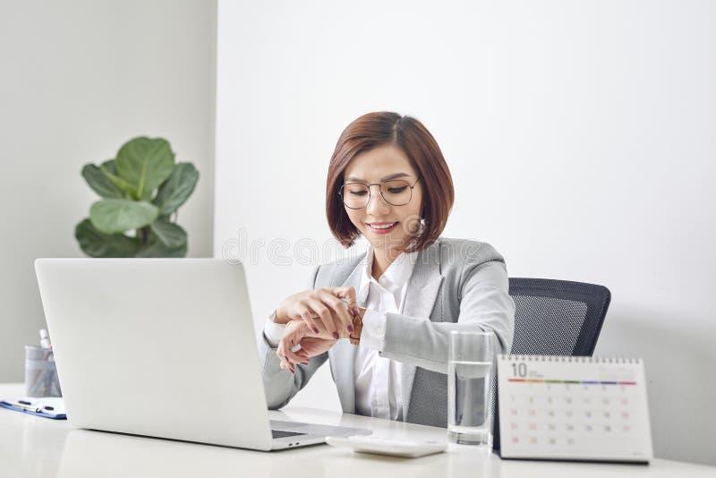 Empresaria joven que comprueba tiempo en su reloj en el lugar de trabajo Gesti?n de tiempo imagen de archivo libre de regalías