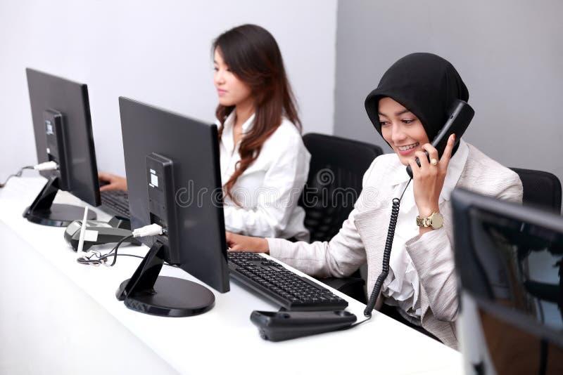 Empresaria joven que contesta al teléfono mientras que trabaja con foto de archivo