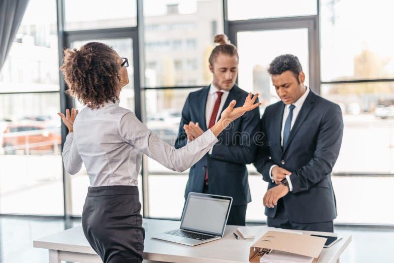 Empresaria joven que gesticula y que discute con los compañeros de trabajo en oficina imagen de archivo libre de regalías