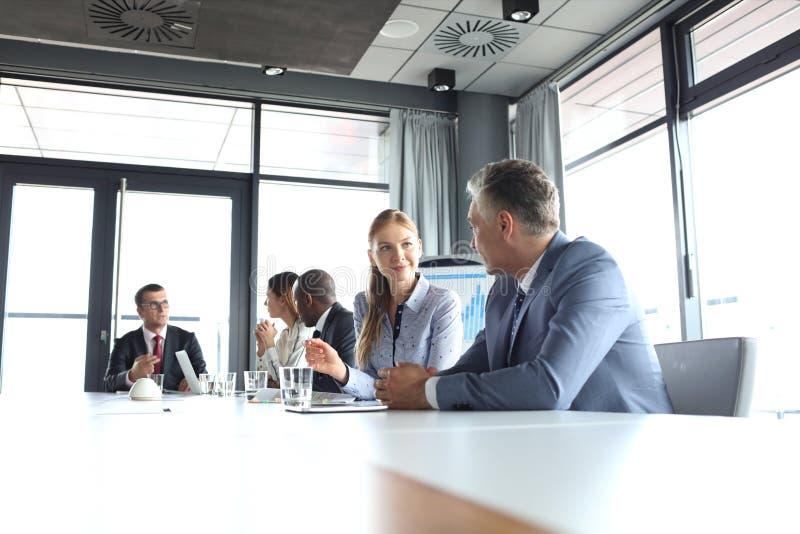 Empresaria joven que habla con el colega masculino en sala de juntas foto de archivo