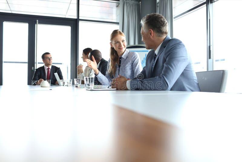 Empresaria joven que habla con el colega masculino en sala de reunión imágenes de archivo libres de regalías