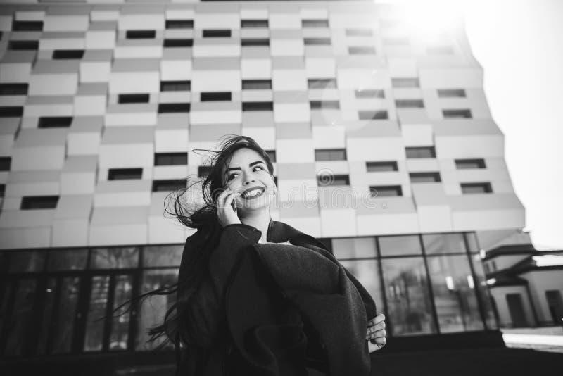Empresaria joven que habla en el tel?fono m?vil durante descanso para tomar caf? al aire libre, cerca del edificio de oficinas Co imagenes de archivo