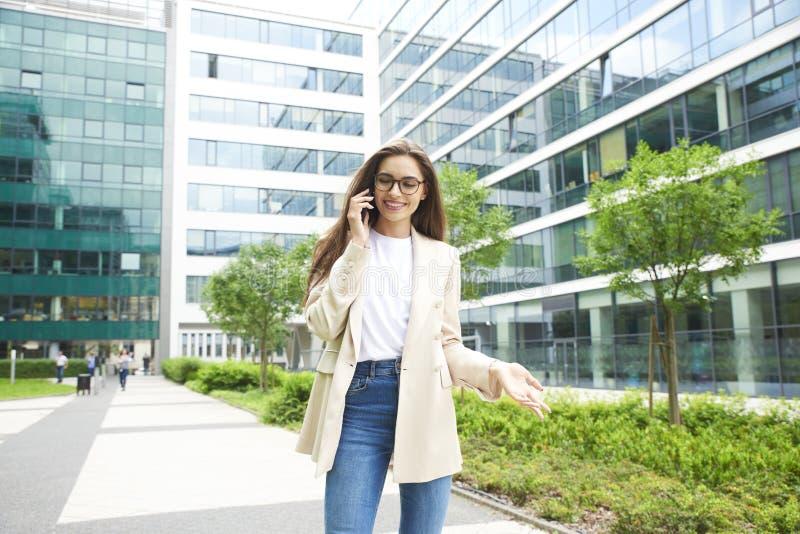 Empresaria joven que hace una llamada mientras que camina en la calle foto de archivo libre de regalías
