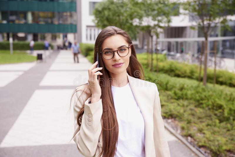 Empresaria joven que hace una llamada mientras que camina en la calle imágenes de archivo libres de regalías