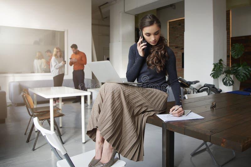 Empresaria joven que hace una llamada mientras que se sienta en el escritorio y el trabajo de oficina imagenes de archivo