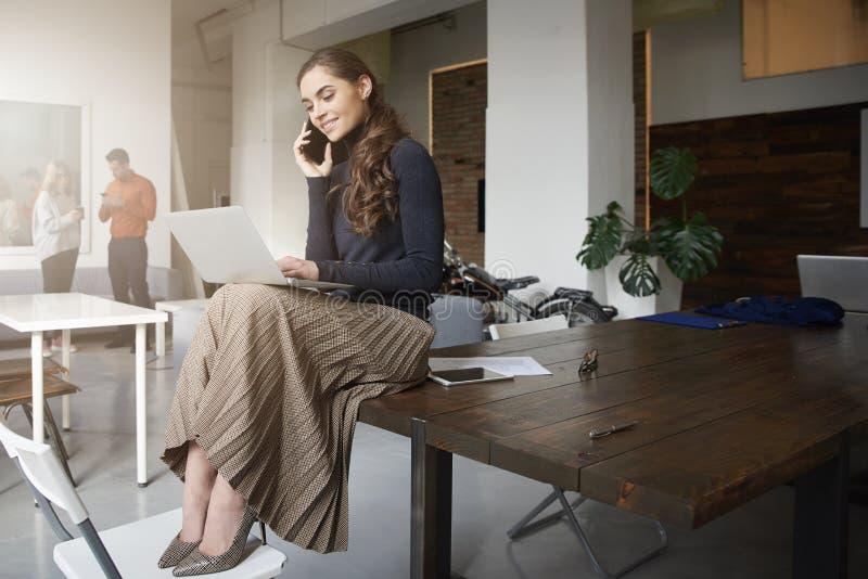 Empresaria joven que hace una llamada mientras que se sienta en el escritorio y el trabajo de oficina imagen de archivo libre de regalías