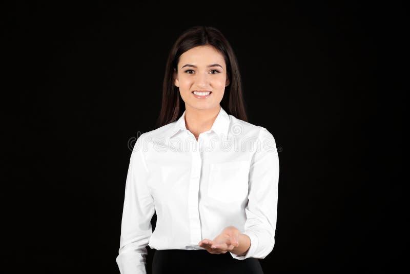 Empresaria joven que lleva a cabo algo en fondo negro foto de archivo libre de regalías