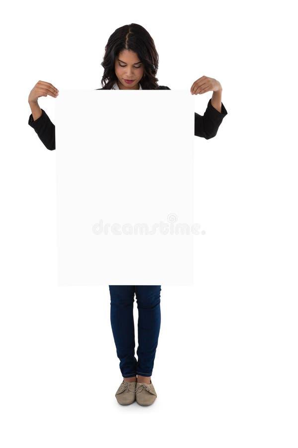 Empresaria joven que lleva a cabo el cartel en blanco fotografía de archivo