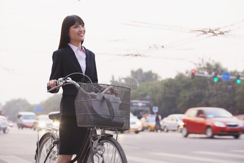 Empresaria joven que monta una bicicleta en la calle, Pekín fotografía de archivo libre de regalías
