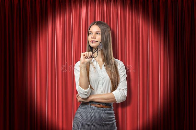 Empresaria joven que piensa y que mira lejos, sosteniendo los vidrios cerca de los labios, colocándose en proyector cerca de la c fotografía de archivo libre de regalías