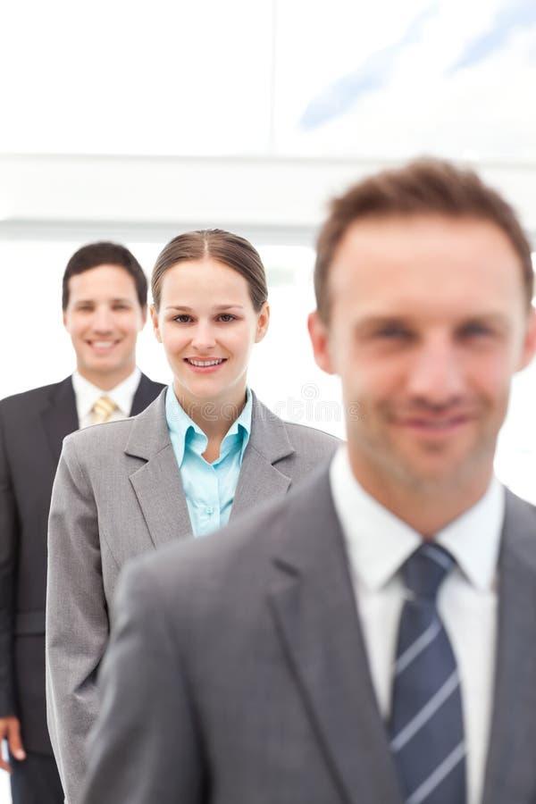 Empresaria joven que presenta con dos hombres de negocios imagen de archivo libre de regalías