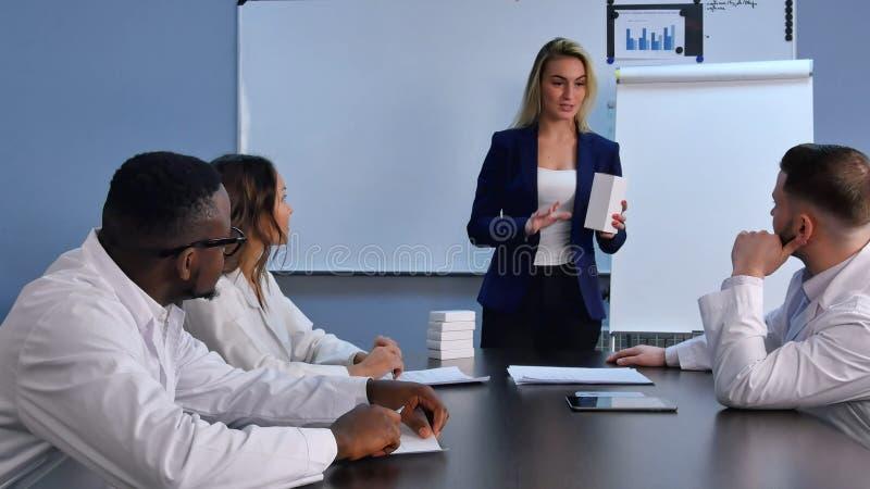 Empresaria joven que presenta las nuevas tabletas o píldoras a los doctores fotografía de archivo