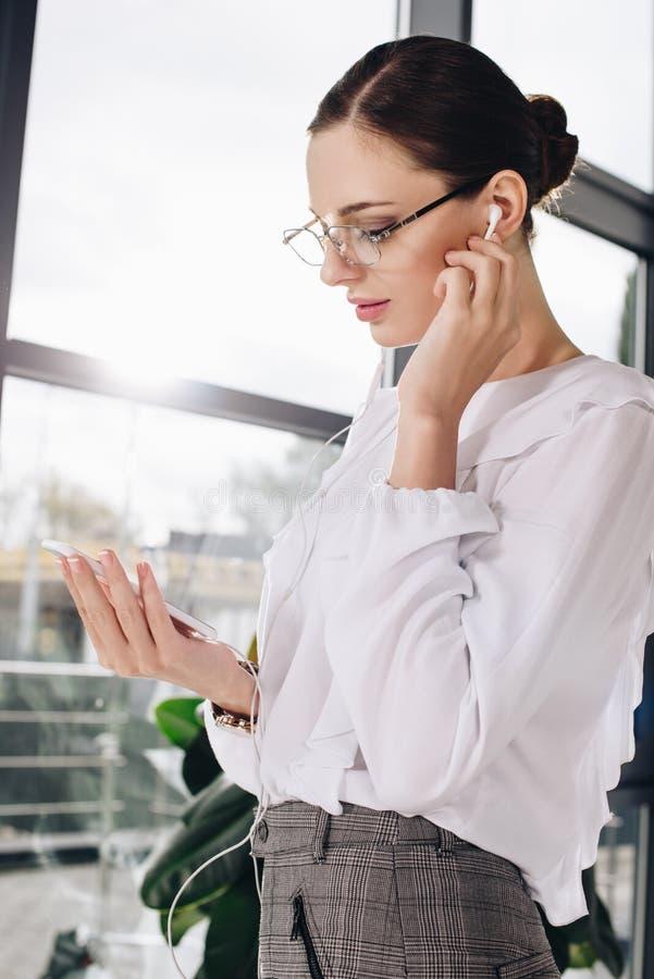 Empresaria joven que se coloca delante de ventana, mientras que escucha la música en auriculares de botón imagen de archivo libre de regalías