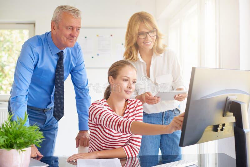 Empresaria joven que se sienta delante del ordenador con sus colegas Trabajo en equipo fotografía de archivo libre de regalías