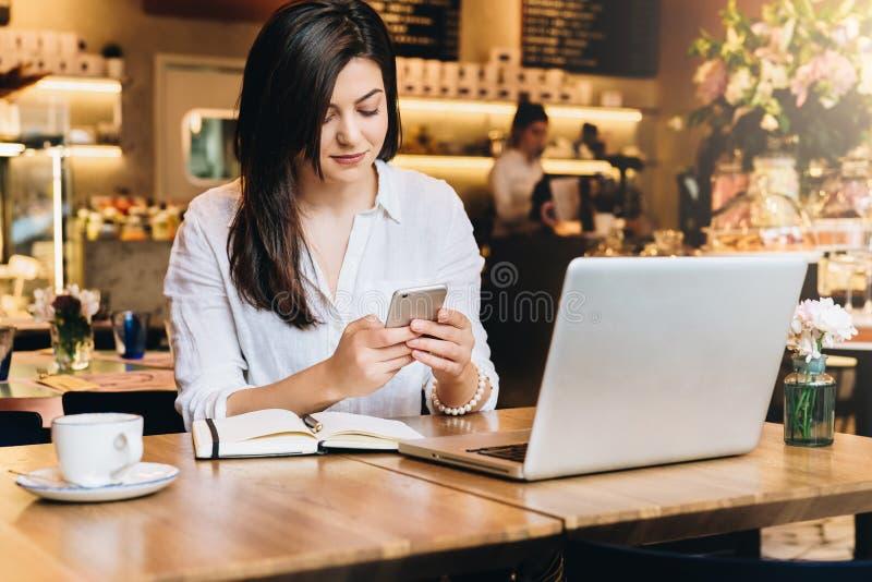 Empresaria joven que se sienta en café en la tabla delante del ordenador portátil y que usa smartphone En el cuaderno de la tabla foto de archivo