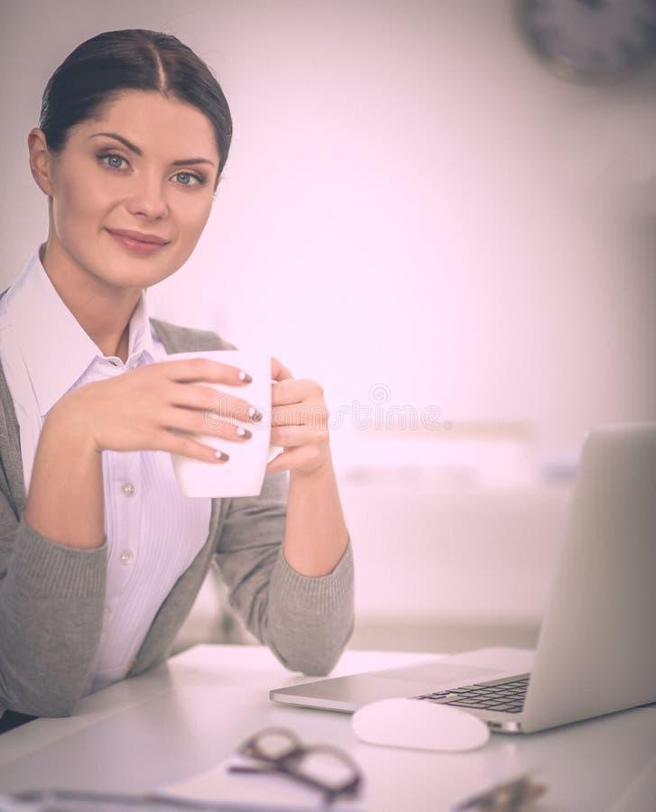 Empresaria joven que se sienta en el escritorio con la taza en oficina fotos de archivo