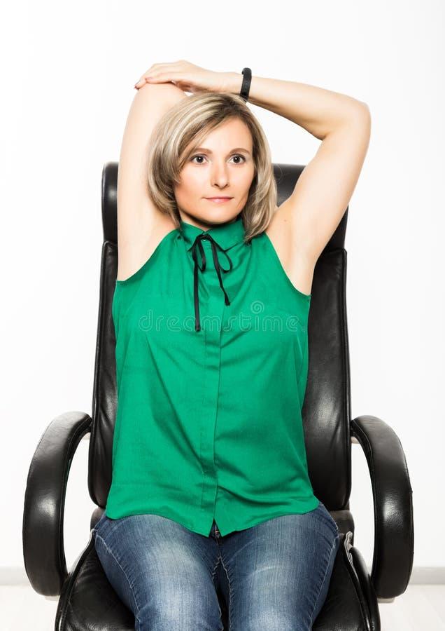 Empresaria joven que se sienta en la silla que hace ejercicio de la aptitud en el lugar de trabajo fotos de archivo