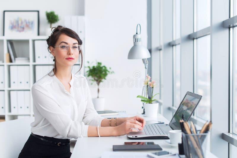 Empresaria joven que se sienta en su lugar de trabajo, resolviendo las nuevas ideas del negocio, traje formal que lleva y vidrios foto de archivo