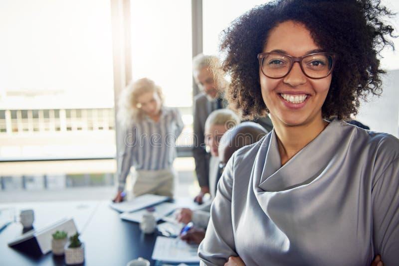 Empresaria joven que sonríe con los colegas que trabajan en el fondo foto de archivo