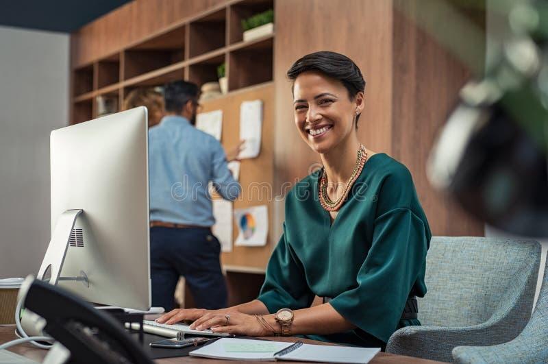 Empresaria joven que sonríe en la oficina foto de archivo
