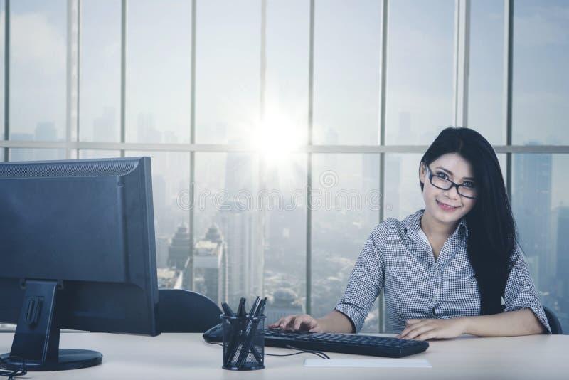 Empresaria joven que sonríe por la ventana imagenes de archivo