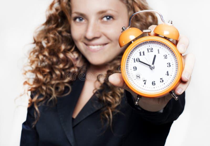 Empresaria joven que sostiene un reloj fotos de archivo libres de regalías
