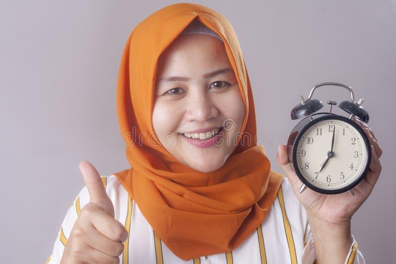 Empresaria joven que sostiene un reloj imagen de archivo libre de regalías