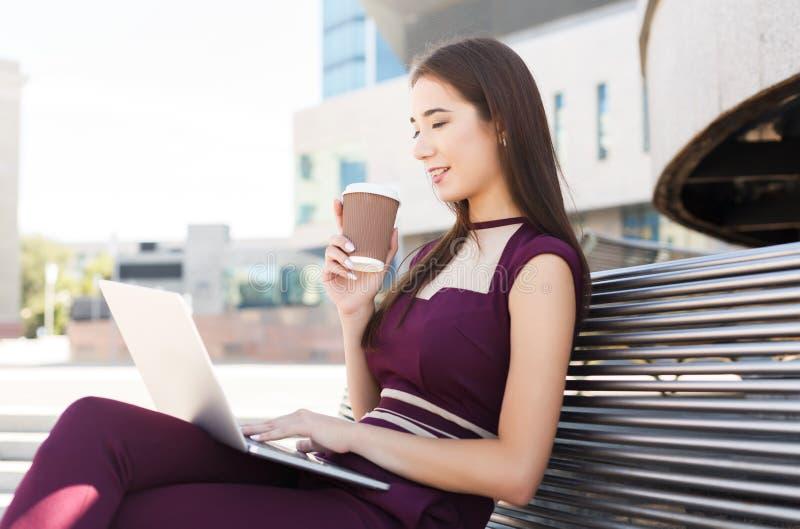 Empresaria joven que trabaja con el ordenador portátil al aire libre fotos de archivo