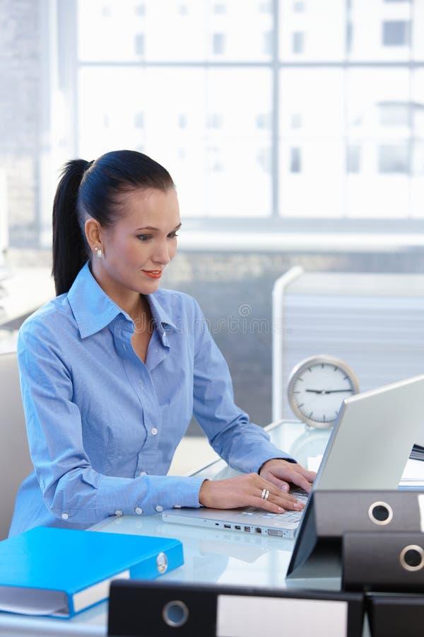 Empresaria joven que trabaja en el ordenador portátil foto de archivo
