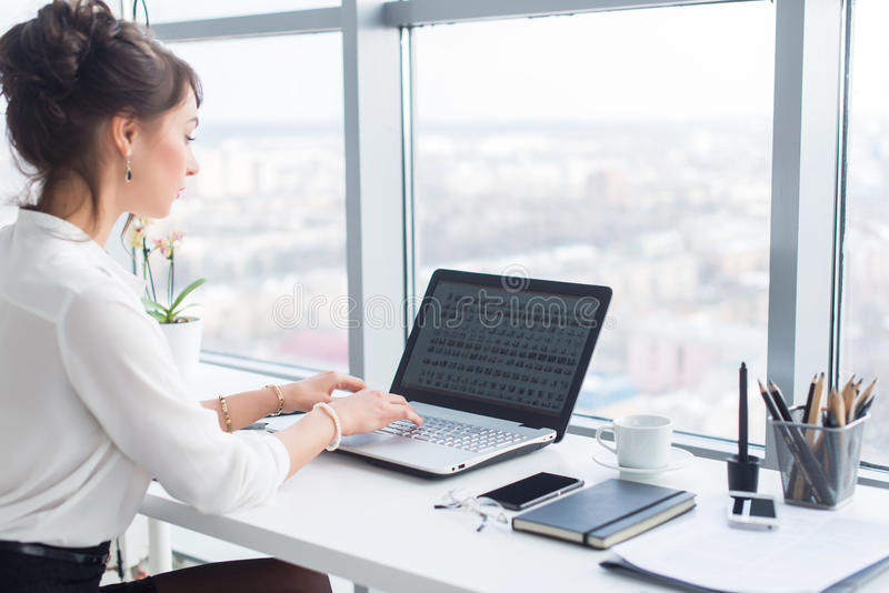 Empresaria joven que trabaja en la oficina, mecanografiando, usando el ordenador Mujer concentrada que busca la información en lí fotos de archivo