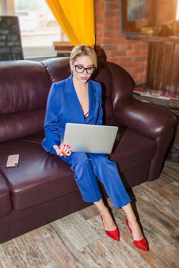 Empresaria joven que trabaja la sentada en línea en el sofá imagen de archivo