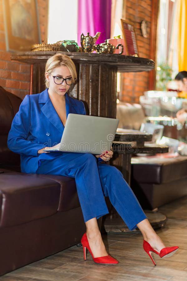 Empresaria joven que trabaja la sentada en línea en el sofá foto de archivo libre de regalías