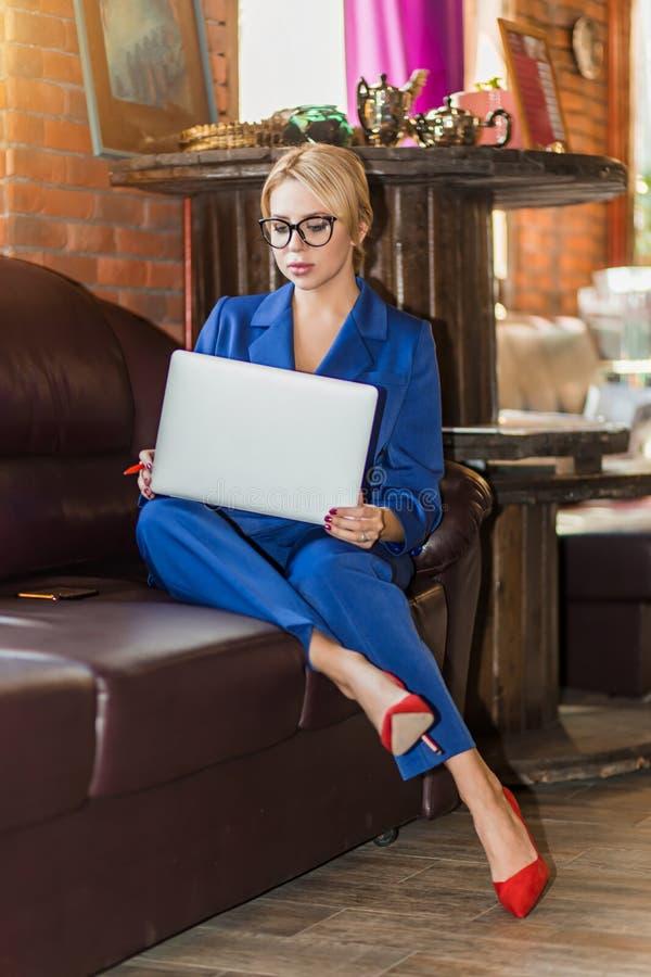 Empresaria joven que trabaja la sentada en l?nea en el sof? foto de archivo