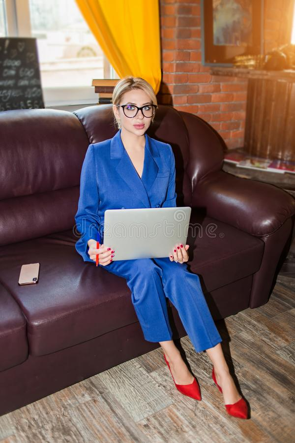 Empresaria joven que trabaja la sentada en l?nea en el sof imagenes de archivo